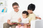 Asian family reading book sitting on sofa indoor, grandparents and grandchild living lifestyle at home.