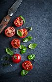 picture of black-cherry  - Halved cherry tomatoes and basil leaves on a black slate  - JPG