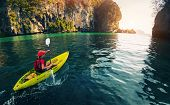 foto of paddling  - Young lady paddling the kayak in the calm bay with limestone mountains - JPG