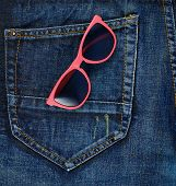 stock photo of denim jeans  - Red sun glasses in a back pocket of a navy blue denim jeans as a background composition - JPG