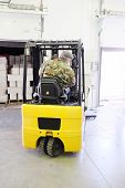 stock photo of forklift driver  - Worker driver stacking boxes by forklift stacker loader - JPG