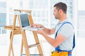 image of step-ladder  - Side view of handyman using laptop by step ladder in bright office - JPG