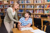 pic of tutor  - Student getting help from tutor in library at the university - JPG