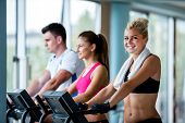 stock photo of treadmill  - Beautiful group of young women friends  exercising on a treadmill at the bright modern gym - JPG