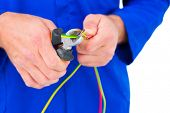 pic of electrician  - Cropped image of electrician cutting wire with pliers over white background - JPG