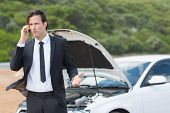 stock photo of breakdown  - Businessman after a car breakdown at the side of the road - JPG