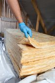 stock photo of glass-wool  - Hand in gloves holding mineral wool building under construction - JPG