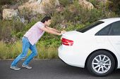 picture of breakdown  - Man pushing car after a car breakdown at the side of the road - JPG