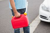 picture of petrol  - Man bringing petrol canister to a broken down car in the street - JPG
