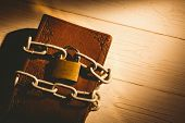 stock photo of pentecostal  - Open bible chained with lock on wooden table - JPG