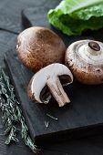 picture of portobello mushroom  - Raw portobello mushrooms with rosemary on cutting board on dark wooden table  - JPG
