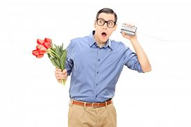 pic of tin man  - Young man holding flowers and listening through a tin can phone isolated on white background - JPG