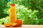 picture of orange  - Bottle of orange juice and the orange and the two orange lobules on the wooden table on the green blurred background - JPG