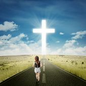 image of rear-end  - Rear view of casual teenage girl walking on the road toward a cross on the end of the road - JPG
