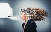 stock photo of wind-power  - Frozen girl under a powerful air conditioner - JPG