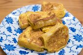 stock photo of french-toast  - A plate of French toast on a white and blue floral designed plate on a wooden table background. ** Note: Shallow depth of field - JPG
