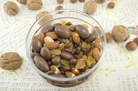 picture of decoupage  - Snack mix of nuts raisinshazelnuts almonds and chocolate in the bowl on a decoupage decorated table - JPG