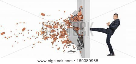 poster of Businessman kicking hard the wall and crush it, side view. Overcoming obstacles. Business issues. Economic development.