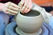 foto of molding clay  - The hands of a potter creating an earthen jar - JPG