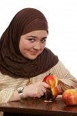 Young veiled woman peeling an apple with a smile