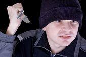 Joven hombre enojado con el cuchillo sobre fondo negro