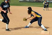 stock photo of fastpitch  - Fastpitch softball firstbase player catches the ball before runner reaches the plate; while runner and shortstop watch from second base. All logos have been removed and team names blurred.