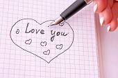 Hand with pen writing a love letter