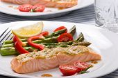 stock photo of salmon steak  - Rosemary roasted salmon served with asparagus cherry tomatoes red bell pepper topped by mustard rosemary sauce and glass of ice water for healthy style dinner - JPG