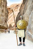 PETRA, JORDAN - OCT 25: Unidentified Bedouin dresses in armor with spear guards roadway into  Siq canyon on October 25, 2010 in Petra, Jordan. Petra is a UNESCO World Heritage Site since 1985.