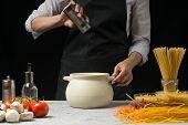 Постер, плакат: Salt In The Chef On A Black Background on The Table Vegetables Spaghetti Pasta Italian Pasta conc