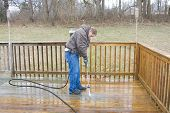 stock photo of pressure-wash  - Worker pressure washing deck on rear of house - JPG
