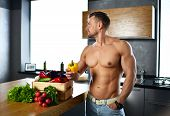 Healthy Strong Muscular Sport Man Standing On Kitchen With Groceries Vegetables Hold Yellow Pepper I poster
