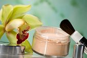 Closeup of container of opened face powder, brush and blooming yellow orchid flower on reflected surface