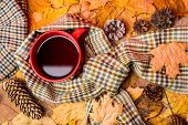 Mug Of Tea Covered Surrounded By Scarf Autumnal Background With Fallen Maple Leaves And Fir Cones. M poster