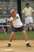 Senior woman at bat in softball game.