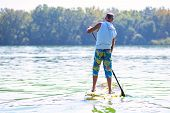 Sporty Man Paddling On A Sup Board On Large River And Enjoying Life. Stand Up Paddle Boarding - Awes poster