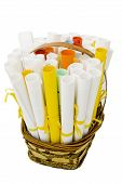 stock photo of gift basket  - wicker basket with paper rolls conceptual symbol of wishes - JPG