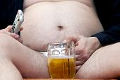 picture of beer-belly  - Overweight man sitting on the couch with a beer glass and remote control - JPG