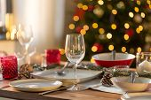 christmas, holidays and table setting concept - wine glass and tableware for festive dinner at home poster