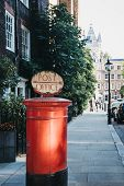 Red Post Box With A Retro Post Office Directional Sign On Top In London, Uk. poster