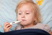 stock photo of high fever  - a sick cute girl is measuring the temperature - JPG