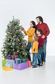 Family Standing Near Mother Decorating Christmas Tree With Presents Isolated On White poster