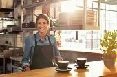 Smiling waitress wearing black apron standing behind counter in cafeteria and looking at camera. Mat poster