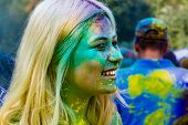Young Energetic Teenagers At The Festival Of Paints Of Holi In Russia. Having Fun Outdoors. Multicol poster