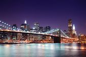 stock photo of new york night  - New York City Brooklyn Bridge and Manhattan skyline with skyscrapers over Hudson River illuminated with lights at dusk after sunset - JPG