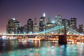 New York City Brooklyn Bridge and Manhattan skyline with skyscrapers over Hudson River illuminated w