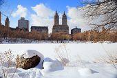 Parque Central de Nueva York Manhattan en invierno con hielo y nieve sobre el lago con rocas, rascacielos un