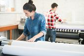 Serious Concentrated Woman In Denim Shirt Standing At Large Format Printer And Choosing Program Whil poster