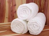 Toallas blancas en un banco de sauna de cedro.