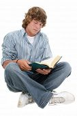 Attractive Sixteen Year Old Teen Boy reading book in casual over white background.  Light brown curl